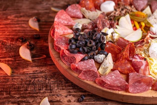 Colpo del primo piano di una varietà di assortimento di carne su una superficie di legno Foto Gratuite