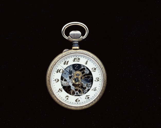 Closeup shot of a vintage pocket watch on a black surface Free Photo