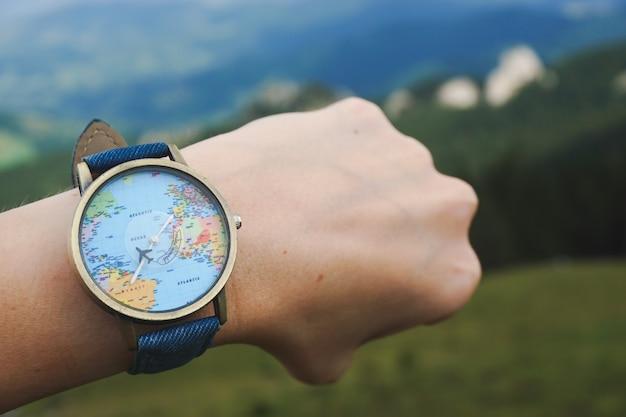 Colpo del primo piano di un orologio legato a una mano con la mappa del mondo su di esso Foto Gratuite