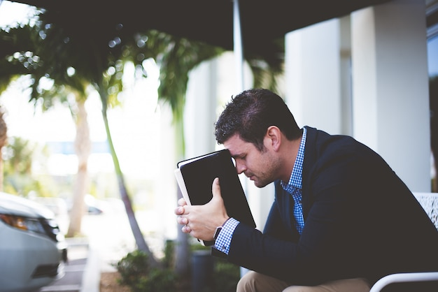 Colpo del primo piano di un maschio ben vestito seduto mentre si tiene la bibbia contro la sua testa Foto Gratuite