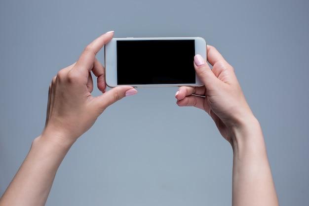Colpo del primo piano di una donna che digita sul telefono cellulare su sfondo grigio. mani femminili che tengono uno smartphone moderno e che indicano con il dito. Foto Gratuite