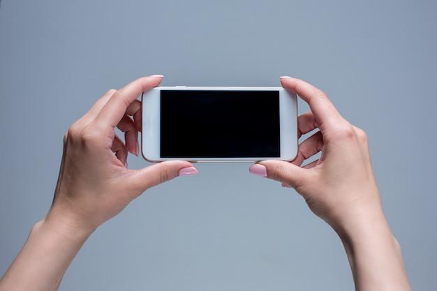 Colpo del primo piano di una donna che scrive sul telefono cellulare Foto Gratuite
