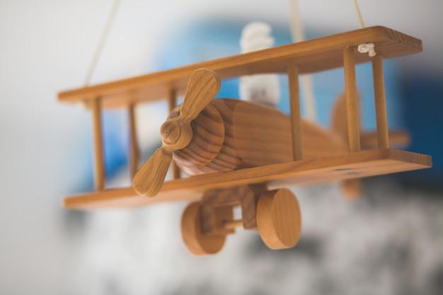 Colpo del primo piano di un vecchio aeroplano in miniatura di legno con uno sfondo sfocato Foto Gratuite