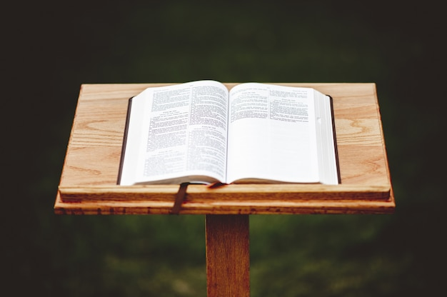 Closeup shot of a wooden speech stand with an opened book Free Photo