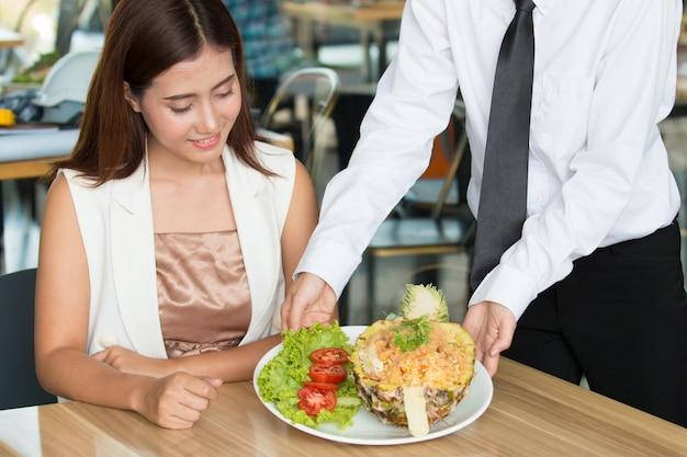 Closeup shot of young woman eating fried rice at restaurant. Premium Photo