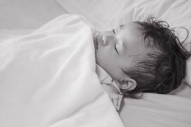 Closeup sick child sleep on hospital bed textured background in black and white tone Premium Photo