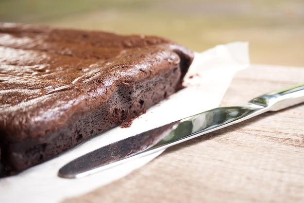 ブラウンイのクローズアップサイド。ナイフはほとんど影をつけている。デザートの背景。 Premium写真