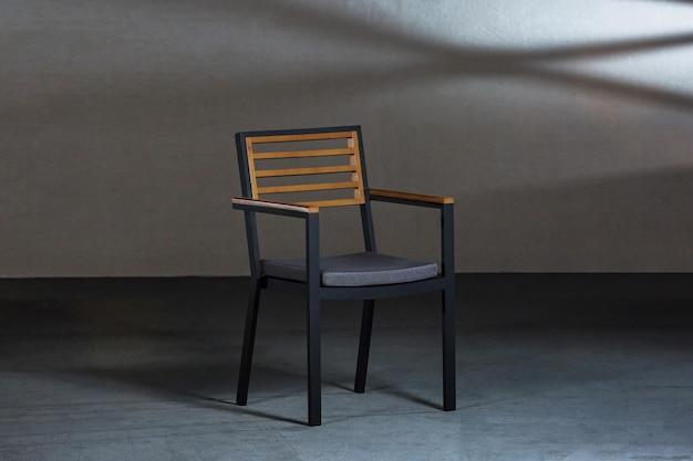 Primo piano di una semplice sedia moderna con gambe metalliche in una stanza con pareti grigie Foto Gratuite
