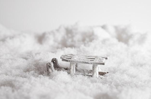 Primo piano di una slitta in mezzo alla neve, giocattolo decorativo di natale sullo sfondo bianco Foto Gratuite