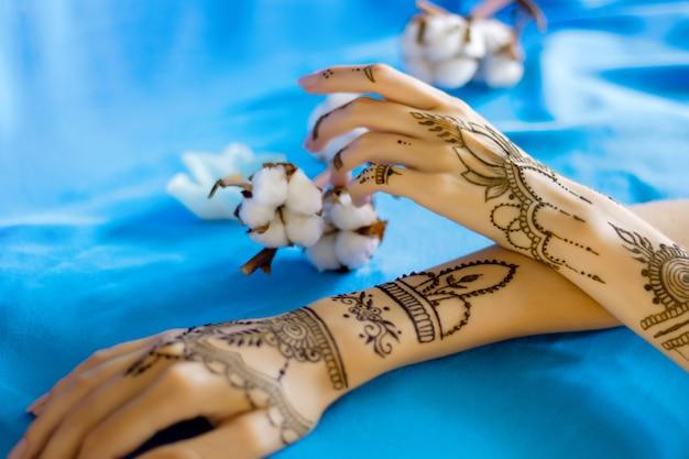伝統的なインドの東洋の一時的な刺青の飾りで描かれたクローズアップのほっそりした女性の手首。ヘナのタトゥーで飾られた女性の手。ひだ、背景に綿の花とスカイブルーの生地。 Premium写真