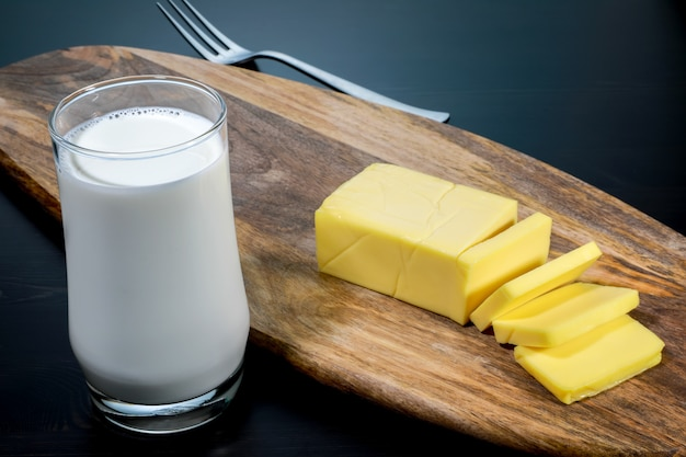 Closeup slice cheese on wooden board with fresh milk in the glass. Premium Photo
