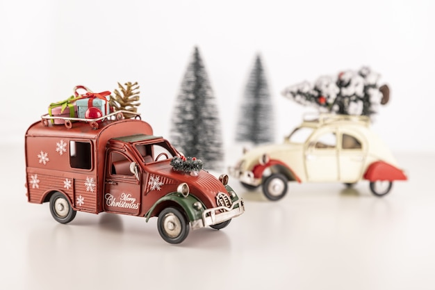 Closeup of small toy cars on the table with small christmas trees in the background Free Photo