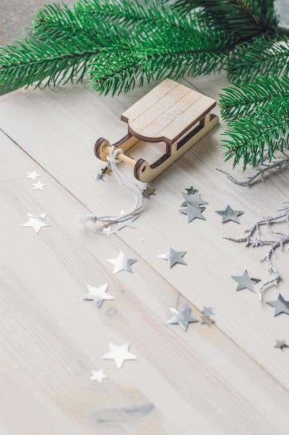 Primo piano di un piccolo ornamento di legno della slitta sul tavolo sotto le luci Foto Gratuite