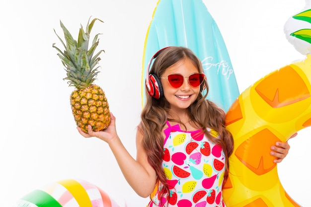 Closeup smiling girl on a white surface, the child holds a pineapple in his hands surrounded by swimming accessories, red headphones on his head Premium Photo