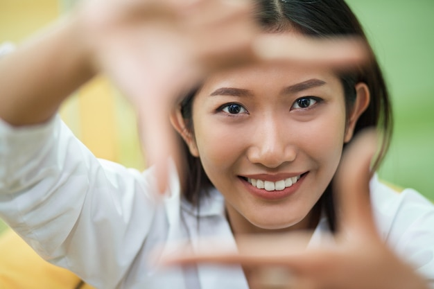 Closeup of smiling woman framing face with fingers Free Photo