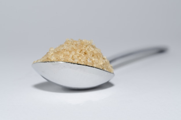 Primo piano di un cucchiaio di zucchero di canna sulla superficie bianca Foto Gratuite