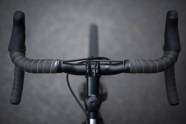 Un primo piano delle maniglie della parte anteriore di una bicicletta di sport ha sparato in bianco e nero Foto Gratuite