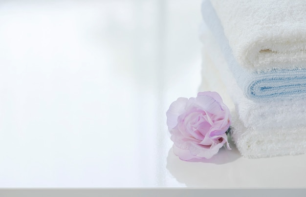 Closeup stack of white towels and flower on white table with copy space. Premium Photo