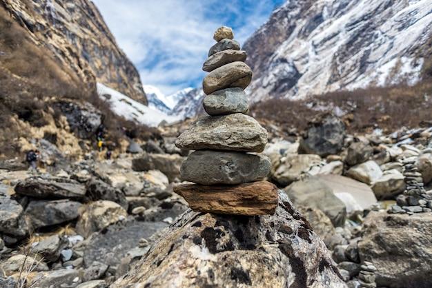 Primo piano di pietre una sopra l'altra circondate da rocce coperte di neve sotto la luce del sole Foto Gratuite