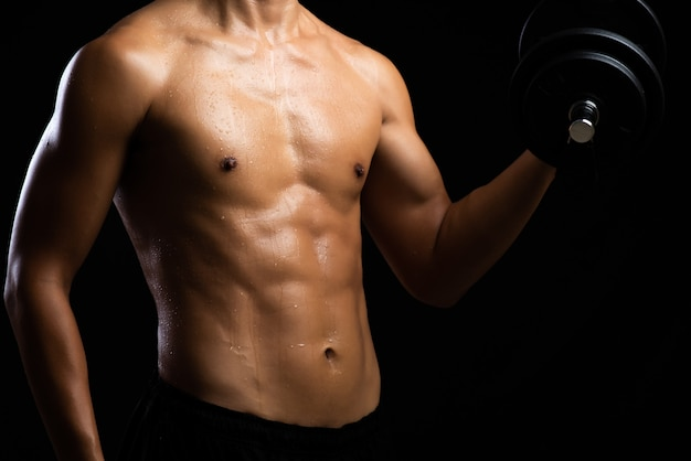 Closeup of a strength fitness body with dumbbell. fit young man Premium Photo