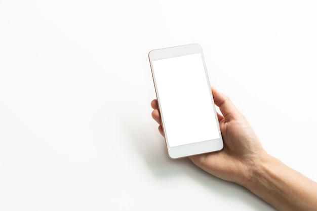 クローズアップスタジオは、スマートフォンの空白の画面を持って手を撮影しました。白い背景で隔離。スペースをコピーします。 Premium写真