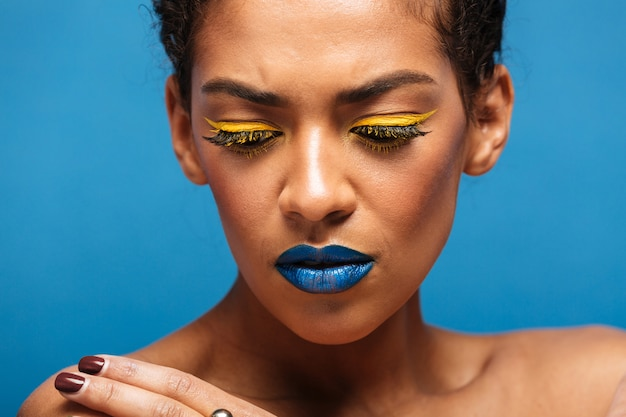 Closeup stylish uptight mixed-race woman with trendy makeup expressing frustration and looking down, isolated over blue wall Free Photo