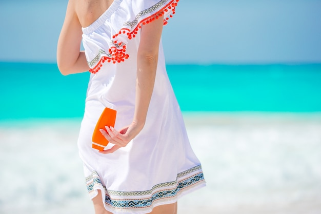 Closeup suncream bottle in female hands on the beach Premium Photo