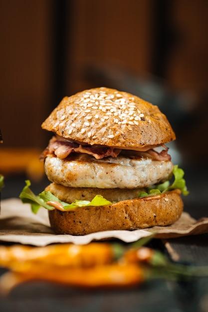 Крупным планом вкусный куриный бургер темный деревянный стол Premium Фотографии