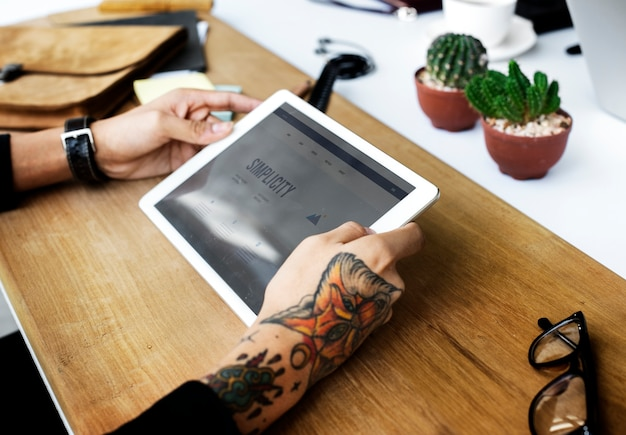81cb032a5 Closeup of tattooed hand holding digital tablet Photo | Free Download
