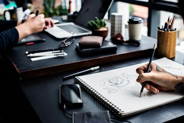 Closeup of tattooed hand with drawing artwork Premium Photo