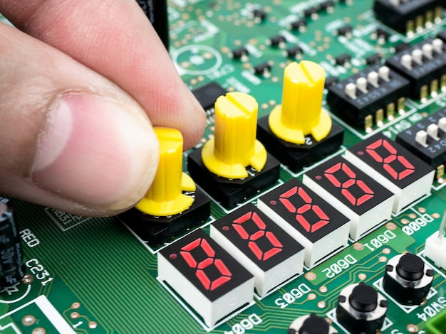 Closeup of a technician's hands checking electronic pcb (printed circuit board) with microchips processor technology Premium Photo
