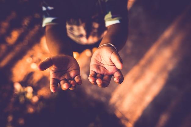 Крупным планом мальчик открытой рукой просить деньги. Premium Фотографии