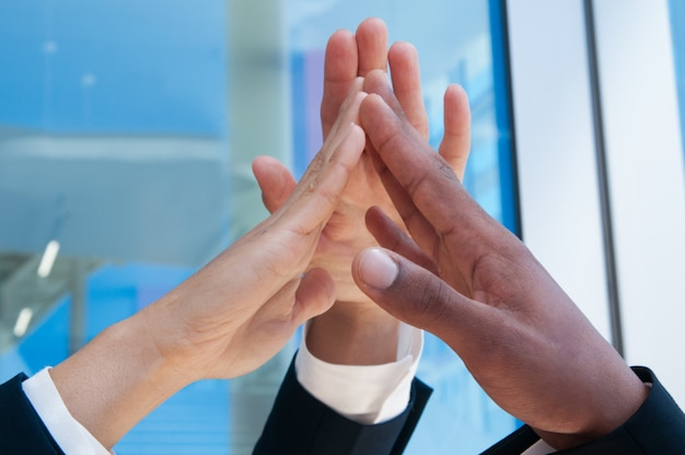 Closeup of three business people high fiving outdoors Free Photo