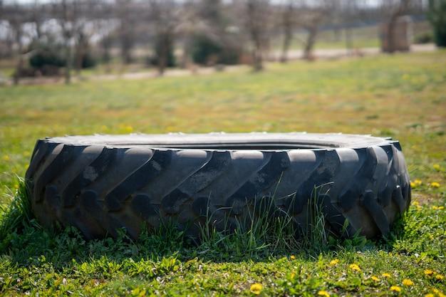 Primo piano di un pneumatico su un campo con fiori gialli Foto Gratuite