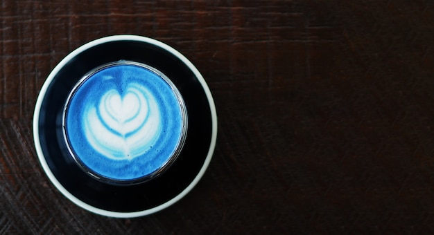 Closeup top view of hot butterfly pea latte on dark wooden table Premium Photo