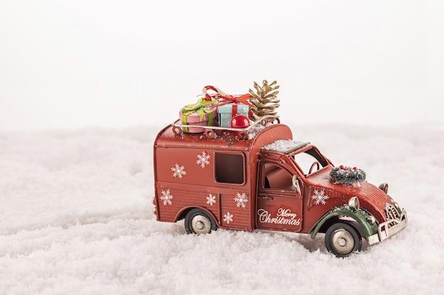 Primo piano di una macchinina con addobbi natalizi su di esso sulla neve artificiale contro uno sfondo bianco Foto Gratuite