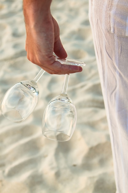 Closeup of two glasses in hand at man walking barefoot on the beach Premium Photo