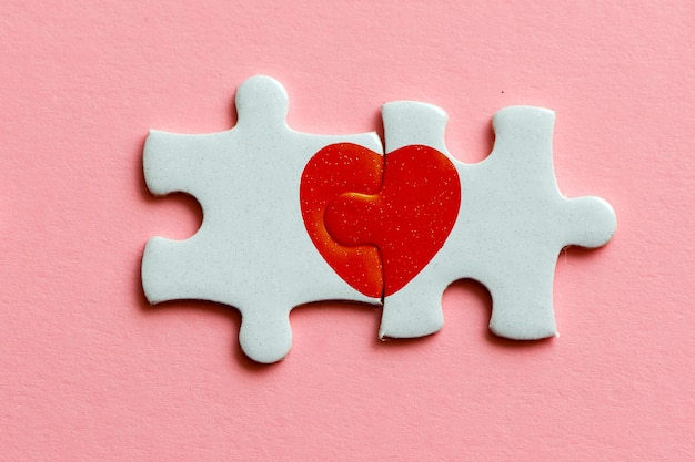 Premium Photo | Closeup of two pieces of a puzzle with red heart on pink  background
