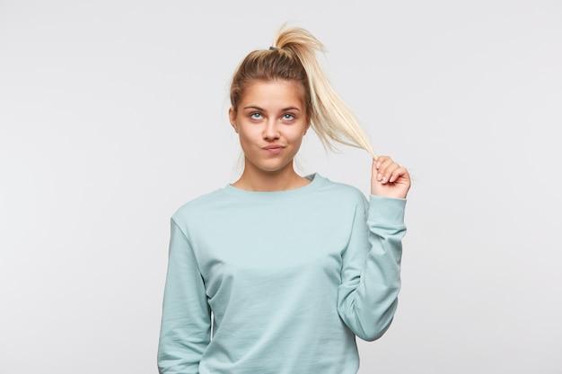 Primo piano di infelice piuttosto giovane donna con capelli biondi e coda di cavallo indossa una felpa blu Foto Gratuite