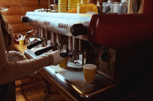 Closeup of unrecognizable barista making coffee in professional coffee machine Premium Photo