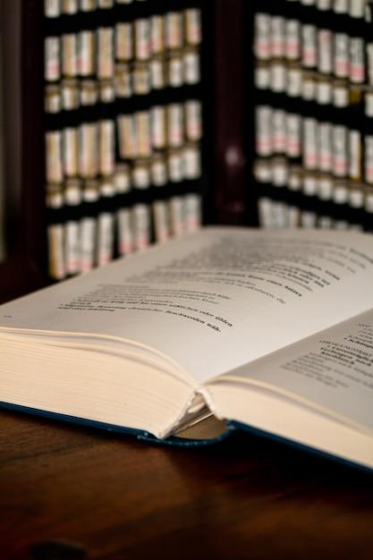 Primo piano colpo verticale di un libro su un tavolo con sfondo sfocato Foto Gratuite