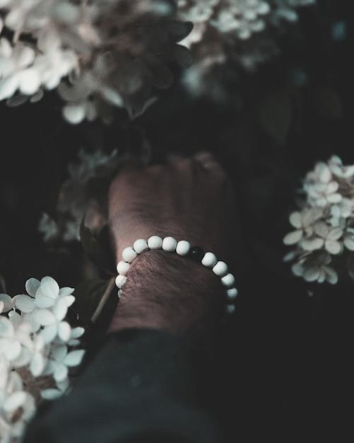 Крупным планом вертикальный снимок мужской руки с белыми и черными бусами, касаясь красивых цветов Бесплатные Фотографии