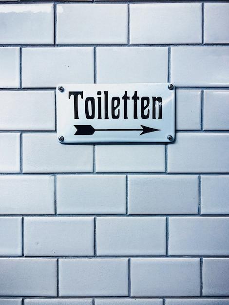 ドイツ語の書き込みとトイレの看板のクローズアップ垂直ショット 無料写真