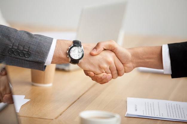 Closeup view of handshake, two businessmen in suits shaking hands Free Photo