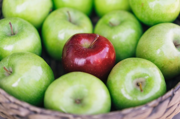 Closeup view of a healthy colorful green apples and one red apple in a basket and the tasty benefits of each. be different Premium Photo
