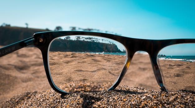 黒い眼鏡のレンズから見たビーチのクローズアップビュー 無料写真