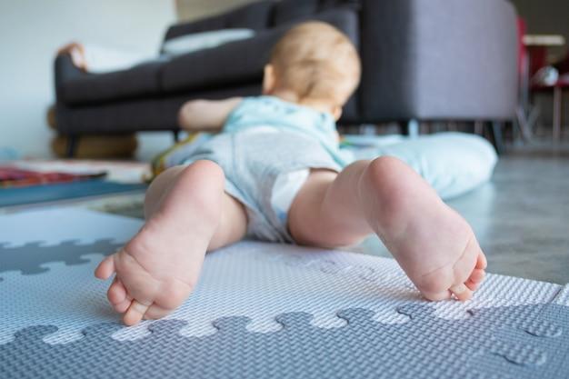 작은 아기 다리 또는 발의 근접 촬영보기입니다. 배꼽에 누워 집에서 부드러운 바닥에 노는 귀여운 사랑스러운 유아. 유년기와 유아기 개념 무료 사진