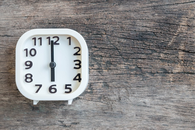Closeup white clock for decorate in 6 o'clock on old wood floor textured background with copy space Premium Photo