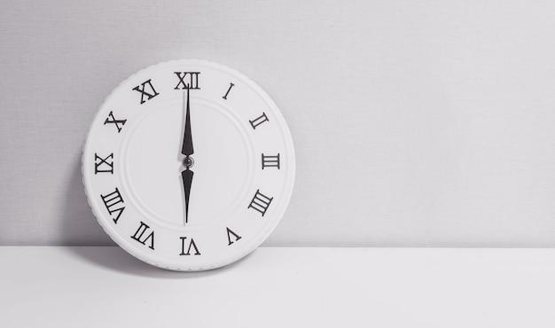 Closeup white clock for decorate in 6 o'clock on wood desk in black and white tone Premium Photo
