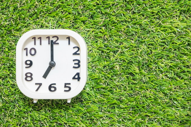 Closeup white clock for decorate in 7 o'clock on green artificial grass floor Premium Photo